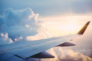 vue de l'aile d'un avion dans le ciel au dessus des nuages